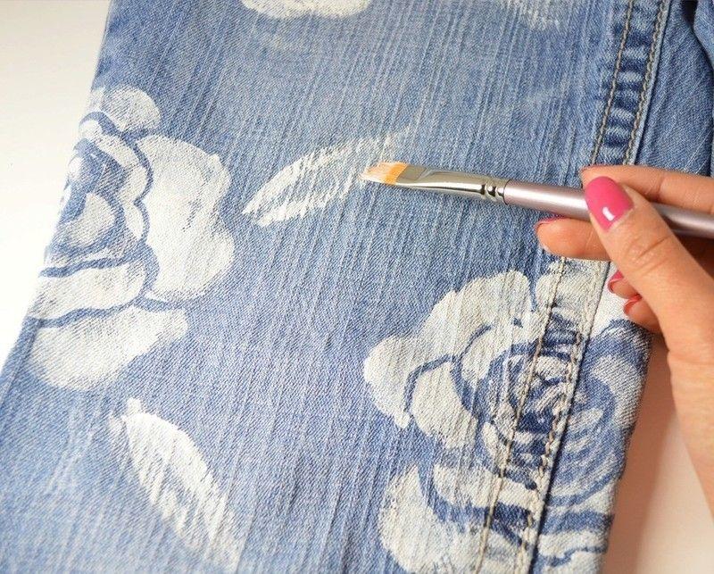 На джинсы кистью наносят рисунок белой краской