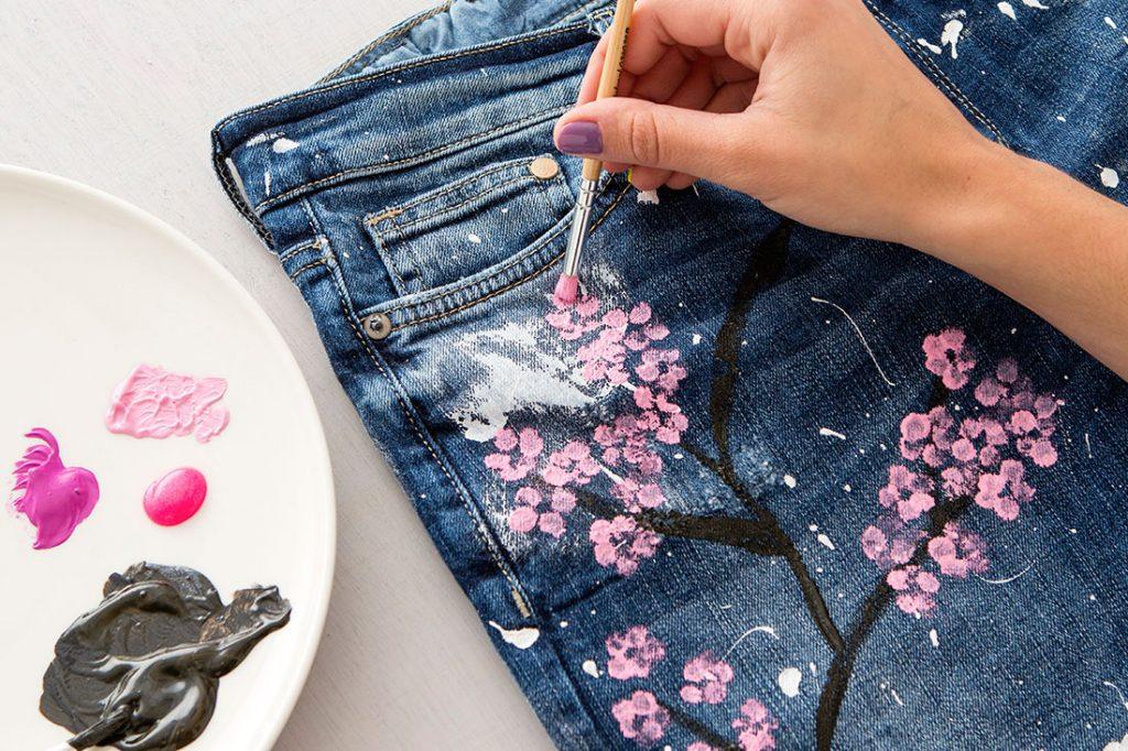 Маленькой кистью на джинсах красками рисуют ветку с цветами