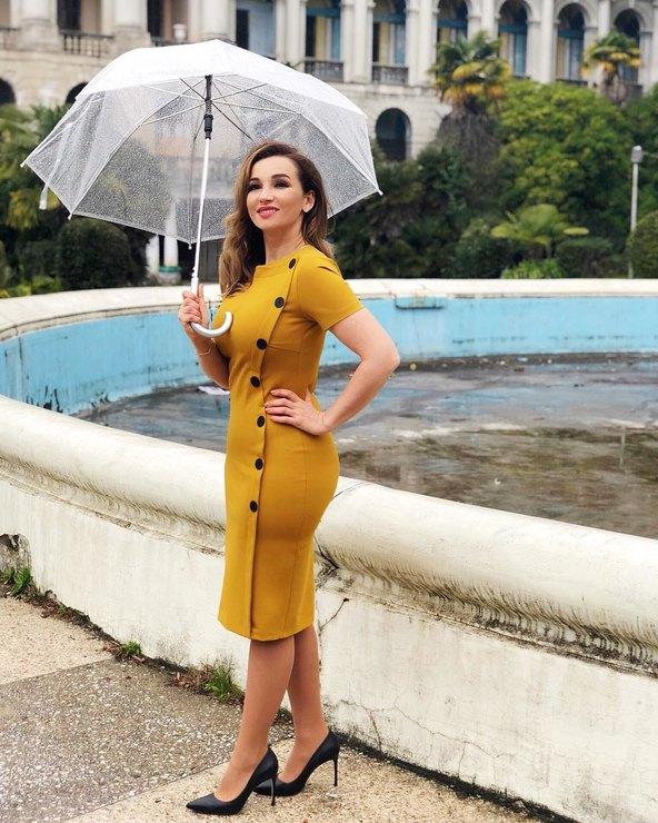 Анфиса Чехова в платье горчичного цвета с прозрачным зонтом