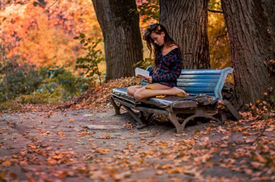 Девушка в парке на скамейке с книгой в руках