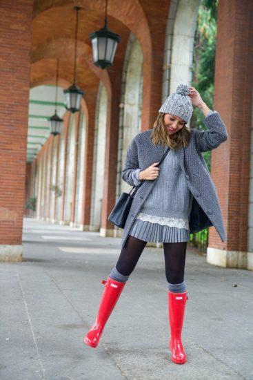 Девушка в серой одежде и красных резиновых сапогах