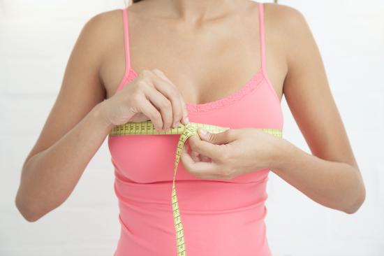 Девушка измеряет грудь сантиметровой лентой