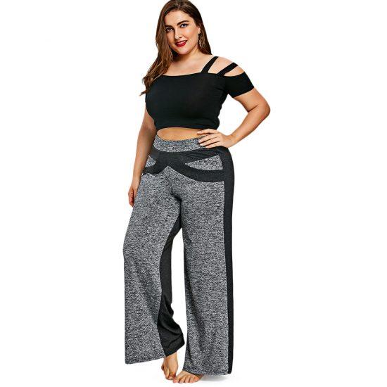 Полная девушка в широких брюках и укороченном топе