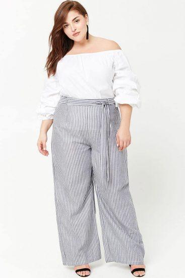 Полная девушка в широких брюках с полоской