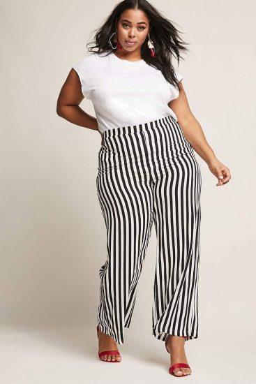 Полная девушка в широких брюках в полоску