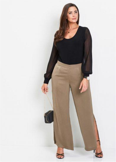 Полная женщина в широких брюках с разрезами