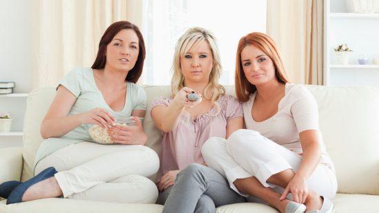 Три девушки на диване смотрят фильм