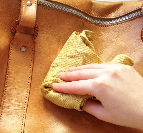 Девушка протирает сумку
