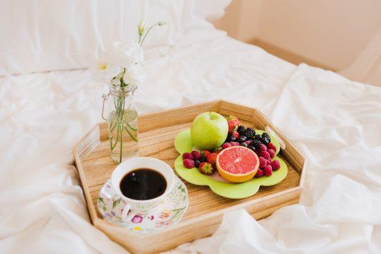 Фрукты, кофе и цветок на подносе в постели