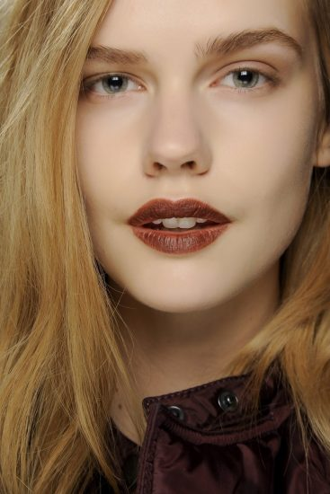 Девушка с выделенными макияжем губами и бровями
