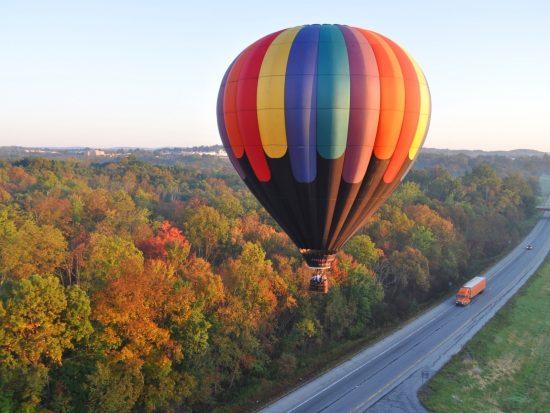 Воздушный шар с пассажирами летит над дорогой