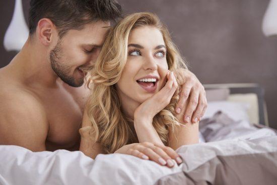 Парень обнимает девушку в постели