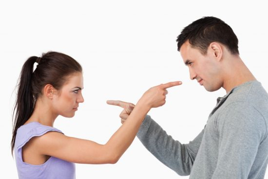 Мужчина и женщина тычут друг в друга пальцами