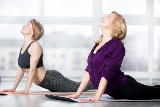 Женщины выполняют упражнения на коврике
