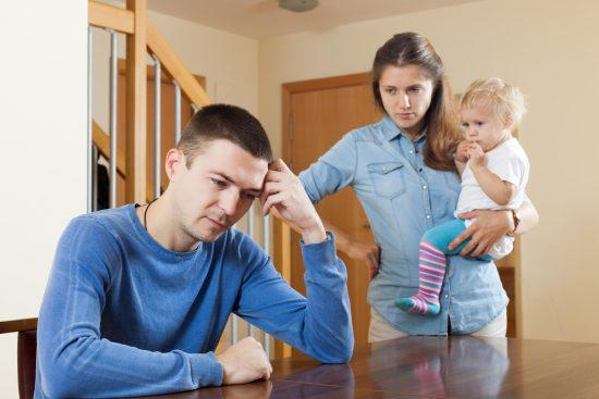 Мужчина сидит за столом, женщина с ребёнком на руках стоит рядом