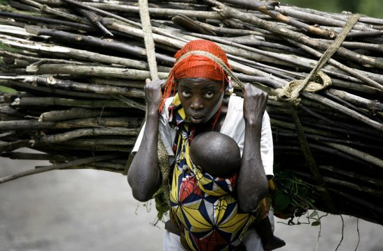 Африканка с младенцем несёт связку дров