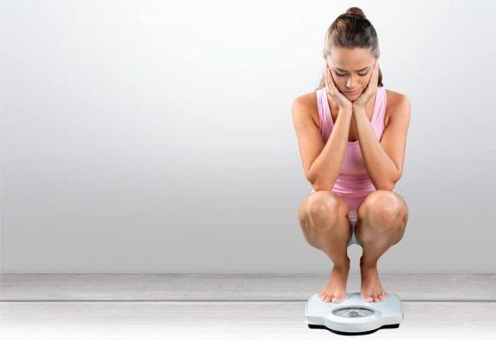 Девушка сидит на напольных весах
