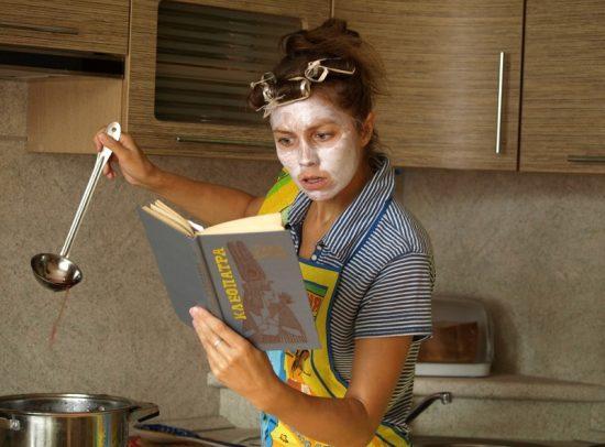 Женщина готовит, читая книгу