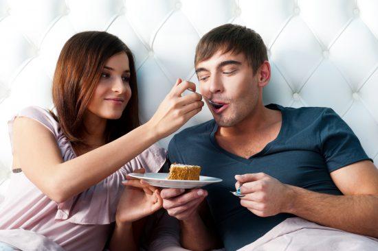 Девушка кормит молодого человека