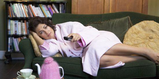 Женщина в халате на диване с пультом от телевизора