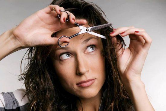 Девушка стрижёт себе волосы