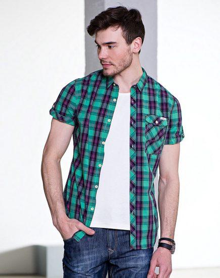 Молодой человек в клетчатой рубашке и белой футболке