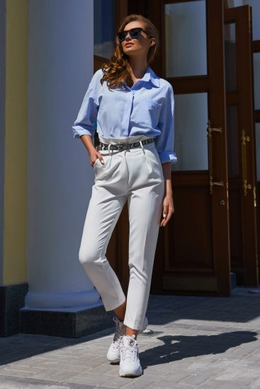 Девушка в белых брюках и кроссовках