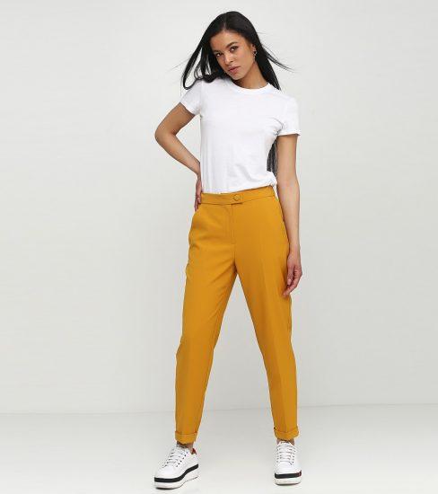 Девушка в брюках со стрелками и кроссовках