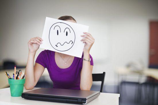 Девушка с рисунком грустной рожицы