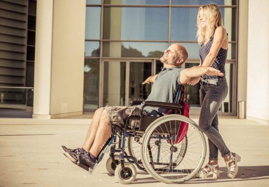 девушка катит мужчину на инвалидной коляске