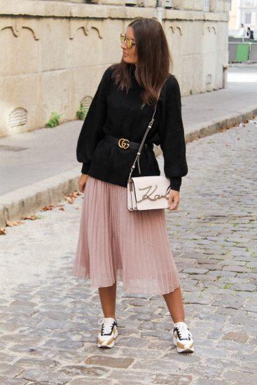 Девушка в плиссированной юбке и кроссовках